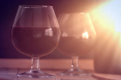 Two wine glass and a bottle on a wooden table against a black background. Sun light. Empty copy space for editor's text Royalty Free Stock Photography