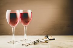 Two Wine glass and corkscrew/Two red Wine glass and wooden corkscrew on a brown background. Selective focus and copyspace royalty free stock image