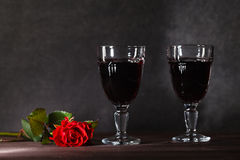 Two wine glass on dark table. With rose Stock Photos