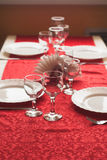 Two wine glass on a red tablecloth, decorated table,. Porcelain plates Royalty Free Stock Photos