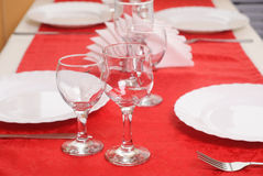 Two wine glass on a red tablecloth, decorated table,. Porcelain plates Royalty Free Stock Photography