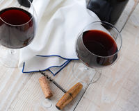 Two Wine Glass Still Life. Two wineglasses of red wine on a wood table with antique cork screw. Horizontal format shot from a high angle Royalty Free Stock Photos