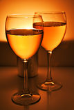 Two wine glasses. Two glasses with white wine over flame of candle Stock Image