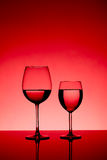Two wine glasses. Filled equally with liquid royalty free stock photo