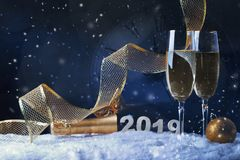 Two wine glasses with champagne, clock and Christmas ornaments on a black background with reflection royalty free stock images