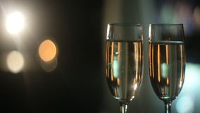 Two wine glasses with champagne. Champagne Pouring from the bottle. Two Flutes with Sparkling Wine over Holiday Bokeh Blinking Background. Couple of champagne stock footage