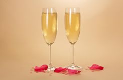Two wine glasses of champagne and rose petals Royalty Free Stock Photography