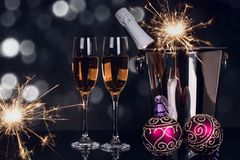 Two wine glasses champagne, sparkler and Christmas ornaments stock photos