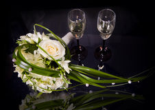 Two wine glasses of champagne and wedding bouquet Stock Images