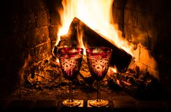 Two wine glasses with chardonnay on the background of a burning fireplace. Two festive crystal glasses with Chardonnay wine. Festive dinner for two near the royalty free stock images