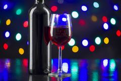 Two wine glasses clink at the party. Christmas concept on a black background, fuzzy lights stock images