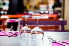 Two wine glasses and cutlery on table in restaurant. Exterior place. Low angle, close up, focus on glasses. Shallow depth of field Stock Photos