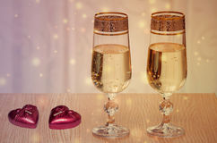Two wine glasses filled with champagne, and candles. Stock Image
