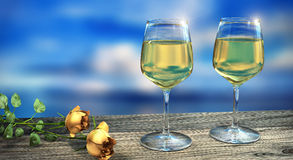 Two wine glasses filled with white wine with two yellow roses in daylight. Two wine glasses filled with white wine with two yellow roses in front of blue sky in Royalty Free Stock Photos
