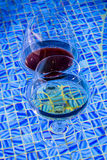 Two wine glasses floating in pool. Royalty Free Stock Photos