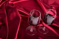 Two wine glasses. With red wine on the red silk Royalty Free Stock Images