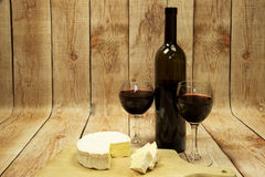Two wine glasses with red wine,bottle of wine and cheese on wood. Two wine glasses with red wine,bottle of red wine and Camembert cheese against the curved Royalty Free Stock Photo