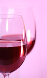 Two wine glasses with red wine closeup. Two wine glasses with red wine on pink background closeup royalty free stock photo