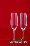 Two wine glasses with rose flower over red Royalty Free Stock Images