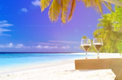 Two wine glasses on sand beach Stock Image