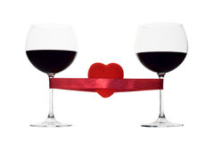 Two wine glasses tied with a red heart Stock Image