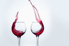Two wine glasses in toasting gesture with big splashing. Stock Image