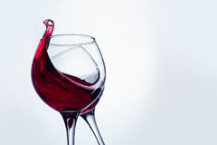 Two wine glasses in toasting gesture with big splashing. Stock Photo