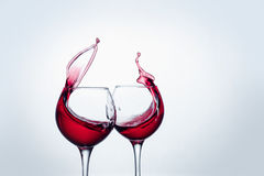 Two wine glasses in toasting gesture with big splashing. Stock Photos