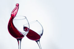 Two wine glasses in toasting gesture with big splashing. Royalty Free Stock Images