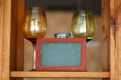 Two wine glasses on wooden shelf with frame Royalty Free Stock Photos