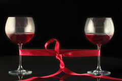 Two wine glasses wrapped with a red tape Royalty Free Stock Photo