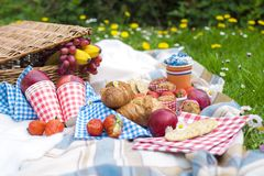 Two wine goblets, fresh strawberry, honey and wine are served for summer romantic picnicPicnic Basket with apples and bread. royalty free stock photography
