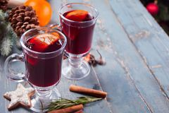 Two wineglass with Christmas mulled red wine with spices and fruits on a wooden rustic table royalty free stock images