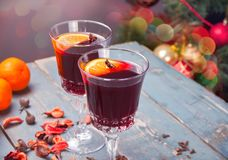 Two wineglass with Christmas mulled red wine with spices and fruits on a wooden rustic table stock photography