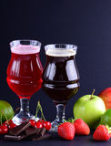 Two wineglasses of craft sweet beer with an assortment of fruits and berries over a black background. Royalty Free Stock Photos