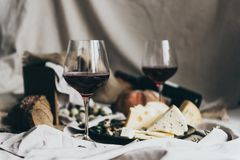 Two wineglasses are filled with dry red wine lying behind. Fresh bread, blue cheese, masdaam cheese and quail eggs are stock image