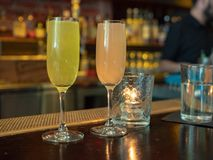 Two wineglasses filled with mimosa drinks sitting on a bar count. Er top during brunch royalty free stock image