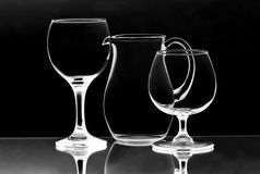 Two wineglasses and a jug on the mirror Stock Images