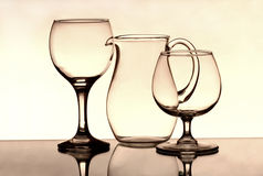 Two wineglasses and a jug on the mirror Royalty Free Stock Images