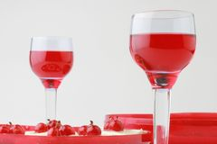 Two wineglasses with red beverage. Two wineglasses of red beverage and dessert with berries on the grey background Stock Image