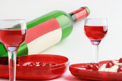 Two wineglasses with red beverage. Two wineglasses of red beverage, wine bottle and dessert with berries on the grey background Royalty Free Stock Photography