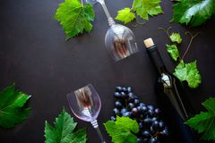 Two wineglasses with red wine, bottle and grape leaves lying on dark wooden background. stock images
