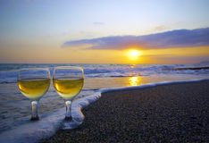 Two wineglasses on the sand and sunset. Two weeping wineglasses on the sand in the wave foam and sunset Royalty Free Stock Photo