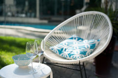 Two wineglasses wand sunbed. Two wineglasses on the small round table with a bowl and sunbed and blurred pool in background Stock Photos