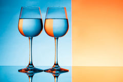 Two wineglasses with water over blue and orange background. Stock Photos