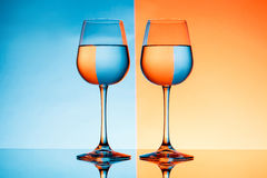 Two wineglasses with water over blue and orange background. Royalty Free Stock Photos