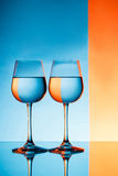 Two wineglasses with water over blue and orange background. Royalty Free Stock Photography