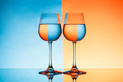 Two wineglasses with water over blue and orange background. Royalty Free Stock Image