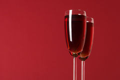 Two wineglasses with wine on the red background Royalty Free Stock Photos