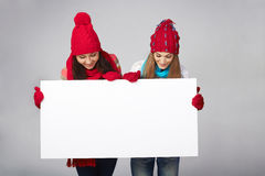 Two winter females with banner Royalty Free Stock Photos
